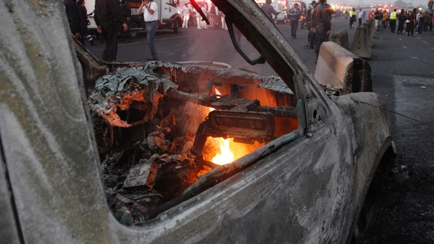 A destroyed car smolders after a gas tanker truck exploded on a highway in the Mexico City suburb of Ecatepec early Tuesday, May 7, 2013. The blast killed and injured dozens, according to the Citizen Safety Department of Mexico State. Officials did not rule out the possibility the death toll could rise as emergency workers continued sifting through the charred remains of vehicles and homes built near the highway on the northern edge of the metropolis. (AP Photo/Gabriela Sanchez)