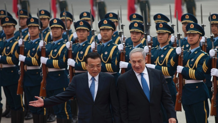 Chinese Premier Li Keqiang, left, gestures to Israeli Prime Minister Benjamin Netanyahu as they review an honor guard during a welcome ceremony outside the Great Hall of the People in Beijing Wednesday, May 8, 2013. (AP Photo/Alexander F. Yuan)