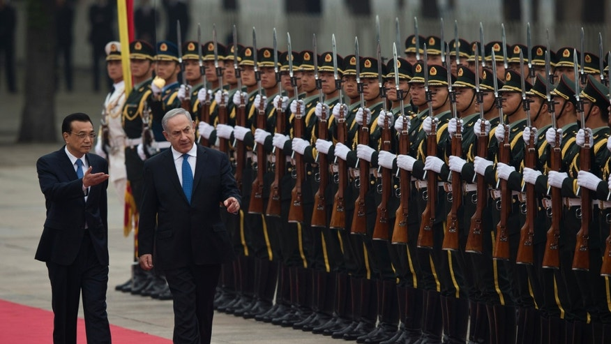 Chinese Premier Li Keqiang, left, and Israeli Prime Minister Benjamin Netanyahu review an honor during a welcome ceremony outside the Great Hall of the People in Beijing Wednesday, May 8, 2013. (AP Photo/Alexander F. Yuan)
