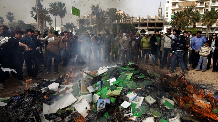 "FILE - In this Wednesday, March 2 , 2011 file photo, Libyan protesters burn copies of Libyan leader Moammar Gadhafi's ""Green Book"" during a demonstration against him in Benghazi, eastern Libya.  A new law that excludes former officials of the Moammar Gadhafi era from public office is dividing Libya and deepening the turmoil that has plagued the country since the civil war that ousted the erratic leader. Passed by lawmakers essentially at gunpoint, it bans not just those who held office but even clerics who glorified the dictator and researchers who worked on his notorious political tract, the Green Book. (AP Photo/Kevin Frayer, File)"