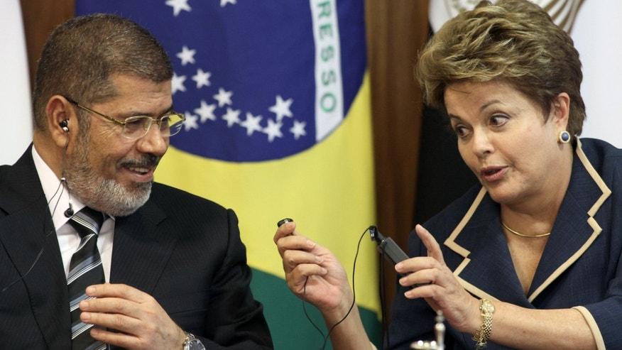 Brazil's President Dilma Rousseff, right, hands an earpiece used for translations to Egyptian President Mohammed Morsi, before the start of a signing ceremony at the Planalto presidential palace in Brasilia, Brazil, Wednesday, May 8, 2013. Morsi is on two-day visit to Brazil. (AP Photo/Eraldo Peres)