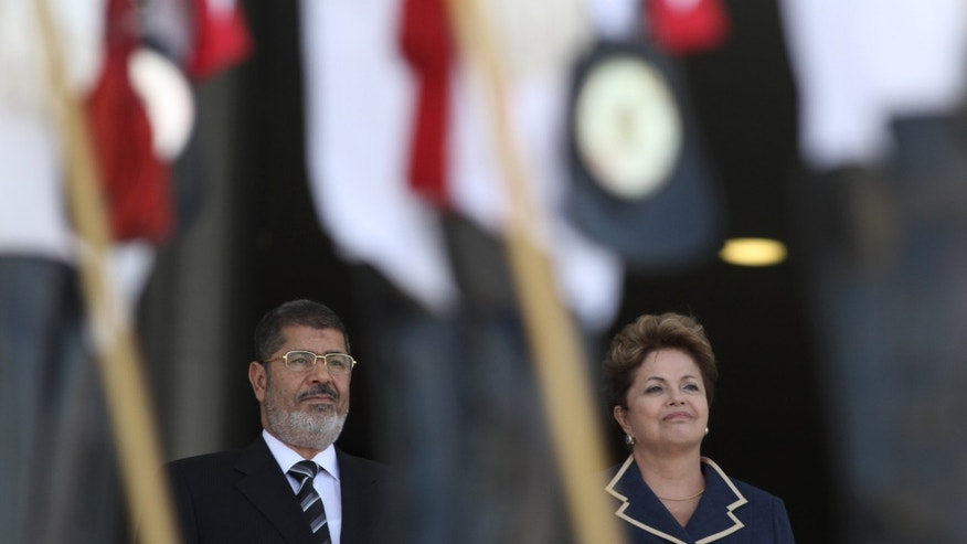 Egyptian President Mohammed Morsi and Brazil's President Dilma Rousseff stand at attention during Morsi's welcome ceremony at the Planalto presidential palace in Brasilia, Brazil, Wednesday, May 8, 2013. Morsi is on two-day visit to Brazil. (AP Photo/Eraldo Peres)