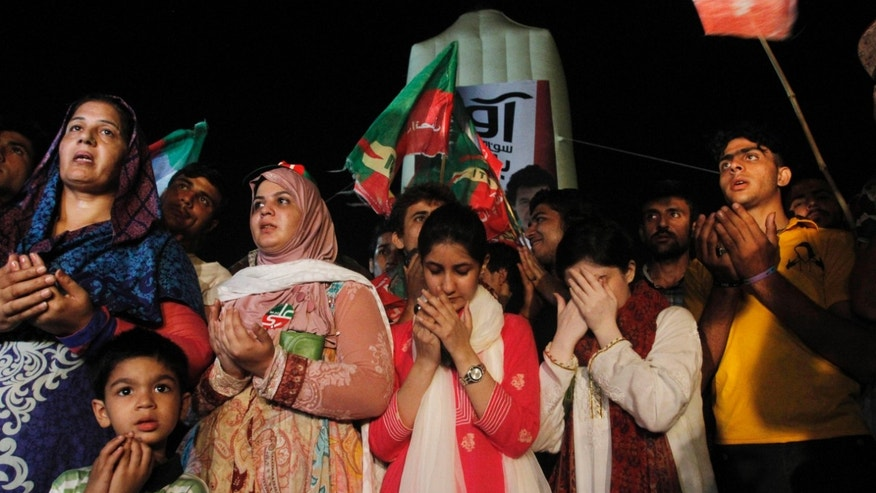 Supporters of Pakistan's cricket star-turned-politician Imran Khan pray for their leader's health in Karachi, Pakistan on Tuesday, May 7, 2013. Pakistan's most prominent politicians, Khan, fell from a stage at a political rally Tuesday in Lahore, leaving him with two hairline skull fractures and uncertainty hanging over his ability to campaign ahead of Saturday's general election. (AP Photo/Shakil Adil)
