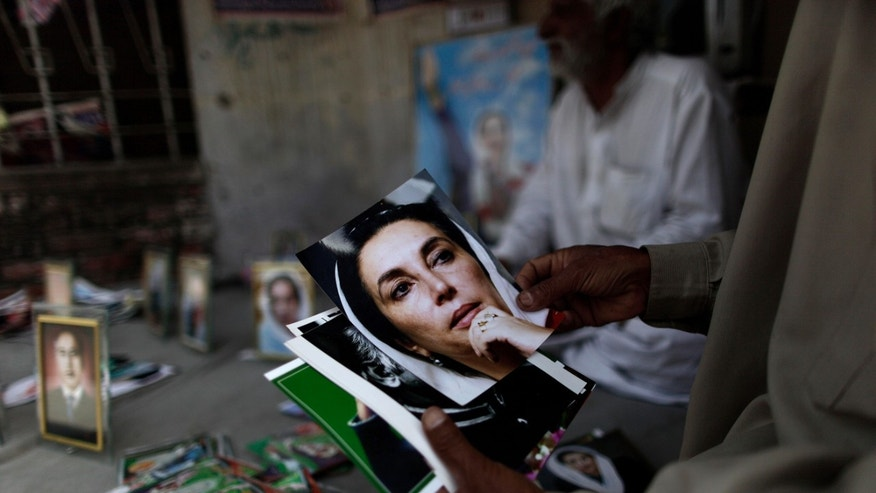 In this Monday, April 8, 2013, photo, a Pakistani man looks at photographs of Pakistan's slain leader Benazir Bhutto, displayed for sale by vendor, Mohammed Ashraf, 65, at the site where she was killed, in Rawalpindi, Pakistan. The campaign posters, fliers and commercials for the Pakistan People's Party are both advertisements for why the party has been so popular and indicate the challenges it faces in the May 11 election: two of the people on the posters are dead and another is not old enough to run in the election. (AP Photo/Muhammed Muheisen)