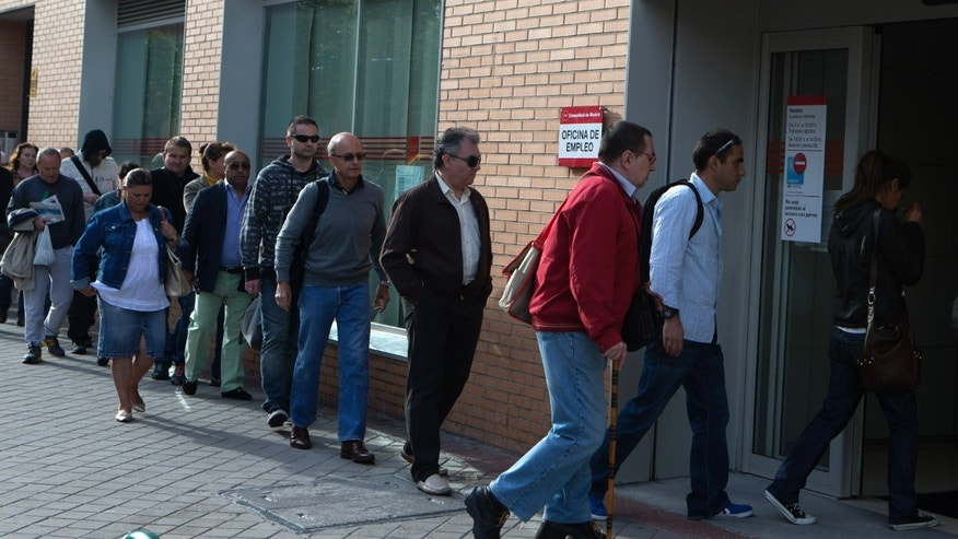 People enter an unemployment registry office in Madrid, Spain Monday May 6, 2013. Spain's Labor Ministry said the number of people registered as unemployed fell by 46,050 in April with more people finding jobs in the run-up to the summer tourist season. Spain has been in recession for the best part of the past four years as the economy battles to recover from the collapse of its once-booming real estate sector. The total number registered as jobless stands at 4.99 million. (AP Photo/Paul White)