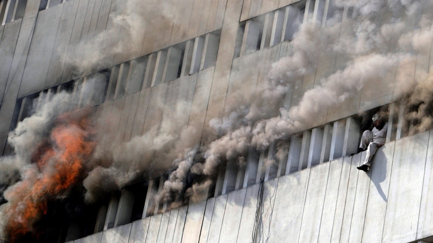 A Pakistani man moments before jumping from the fifth floor of a building that caught on fire in Lahore, Pakistan, Thursday, May 9, 2013. The 13-storey government building caught fire and quickly intensified spreading to three floors of the tall building. (AP Photo/K.M. Chaudary)