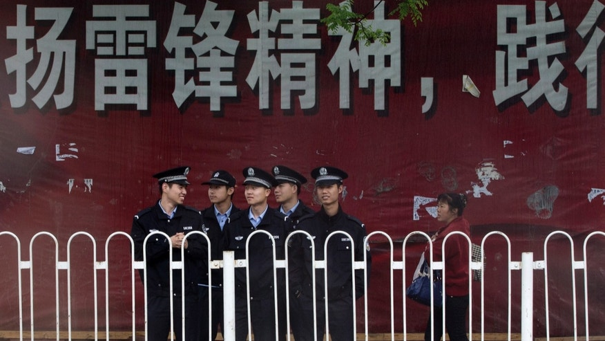A Chinese woman walks by a troop of policemen near a clothing wholesale mall where a woman fell to her death on May 3, in Beijing Thursday, May 9, 2013. With anti-riot vans and helmeted paramilitary forces, police in China's capital smothered a southern district for a second day Thursday after a protest by hundreds of migrant workers, underscoring the authorities' sensitivity over unrest driven by anger over social inequality. (AP Photo/Andy Wong)