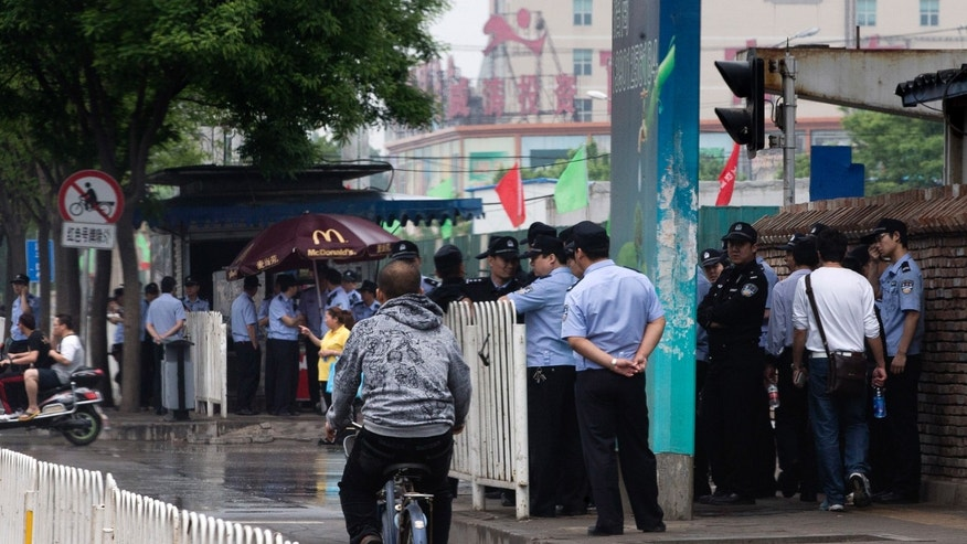 Chinese policemen stand guard on a pavement near a clothing wholesale mall where a woman fell to her death on May 3, in Beijing Thursday, May 9, 2013. With anti-riot vans and helmeted paramilitary forces, police in China's capital smothered a southern district for a second day Thursday after a protest by hundreds of migrant workers, underscoring the authorities' sensitivity over unrest driven by anger over social inequality. (AP Photo/Andy Wong)