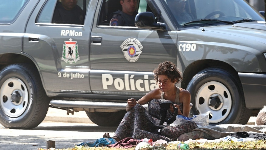 "A suspected crack user sits on the side of a street as police patrol the neighborhood popularly known as ""Crackland"" in downtown Sao Paulo, Brazil, Thursday, May 9, 2013. Sao Paulo State Governor Geraldo Alckmin announced the upcoming launch of a program that gives families of crack cocaine abusers money to pay for their rehabilitation in private treatment centers. The plan announced Thursday earmarks $650 a month for each crack user aged 18 or over who voluntarily enrolls in a rehabilitation program expected to get under way in two months in 11 cities. The city of Sao Paulo is not included because users in the state capital are attended by a network of public treatment centers. (AP Photo/Andre Penner)"