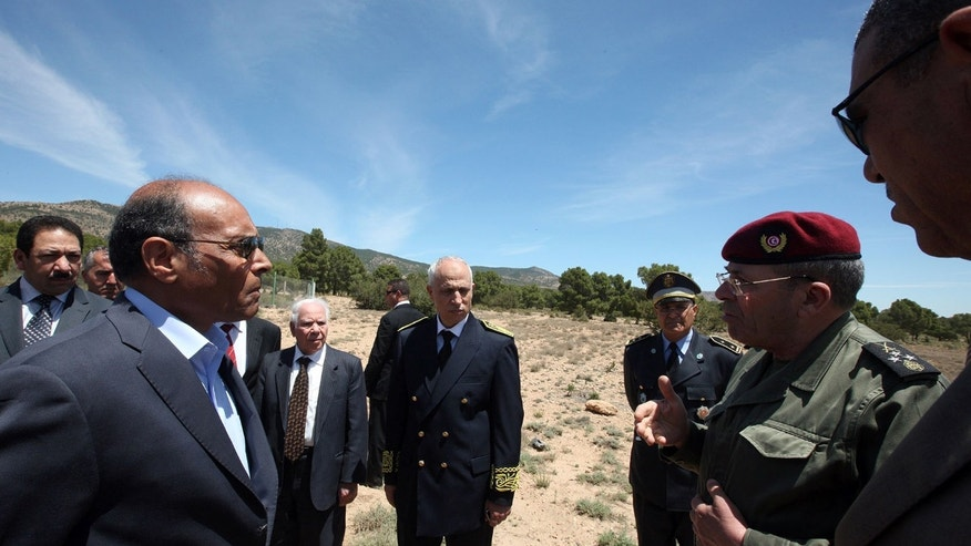 This photo provided by the Tunisian Presidency shows Tunisian President Moncef Marzouki, left, and Chief of Staff Rachid Ammar, second right, visiting military forces in Jebel Chaambi, western Tunisia and close to the Algerian border, Tuesday, May 7, 2013. Tunisia's Defence Ministry says the army has surrounded a group of armed militants holed up in a mountain stronghold protected by homemade fertilizer bombs. (AP Photo/Tunisian Presidency)