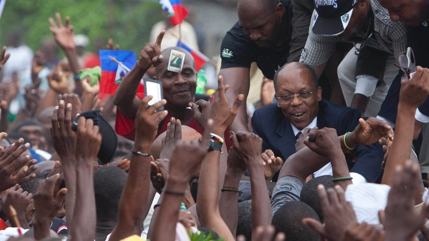 Former Haitian President Jean-Bertrand Aristide, right, greets supporters outside the courthouse in Port-au-Prince, Haiti, Wednesday, May 8, 2013. Aristide greeted a small group of onlookers after testifying before a judge investigating the slaying of one of the country's most prominent journalists. The judge is questioning Aristide about the killing in April 2000 of Jean Dominique, a friend of the former president. (AP Photo/Dieu Nalio Chery)