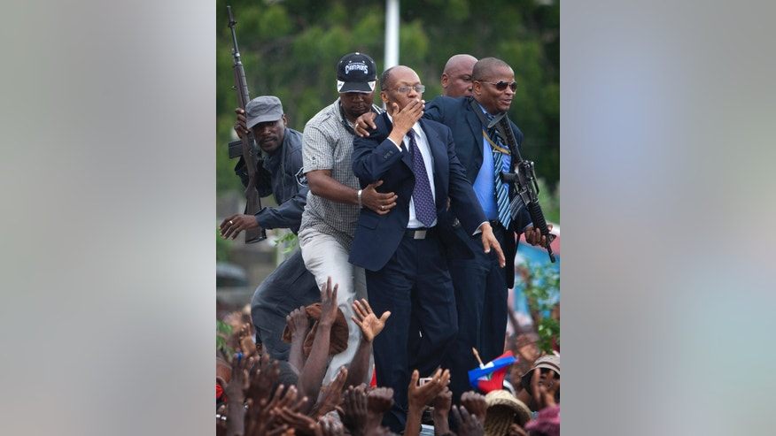 Flanked by body guards, former Haitian President Jean-Bertrand Aristide, center, greets supporters as he leaves the courthouse in Port-au-Prince, Haiti, Wednesday, May 8, 2013. Aristide greeted a small group of onlookers after testifying before a judge investigating the slaying of one of the country's most prominent journalists. The judge is questioning Aristide about the 2000 killing of Jean Dominique, a friend of the former president. (AP Photo/Dieu Nalio Chery)