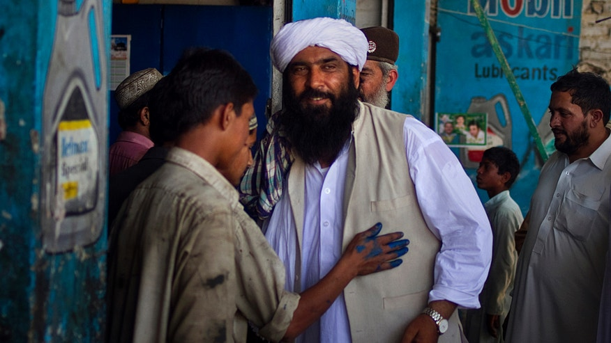"""In this Thursday, May 2, 2013 photo, Maulana Shujaul Mulk, center, pro-Taliban Jamiat-e-Ulema Islam (JUI-F), meets with workers during his election campaign at a market in Mardan, Pakistan. Mulk is among several Pakistani Islamists and sectarian groups contesting for the country's upcoming parliamentary elections, which are divided and scattered though, they are still in a position to secure enough strength to play Pakistani establishment bid to """"hound"""" the next frail government in influencing its decisions about the U.S. forces withdrawal from Afghanistan in 2014. (AP Photo/Anjum Naveed)"""