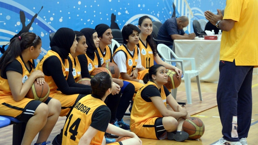 May 9, 2013: Kuwait's Qadsiya Club women basketball team listen to their coach, during the Women's Games, at Salwa Al Sabah Sports Center in Qurein, Kuwait. The event is part of a new initiative launching sports leagues for women, including basketball, table tennis and athletic leagues for the first time in Kuwait illustrating how the landscape for women athletes is improving across the Persian Gulf where hard-liners have long opposed women playing sports.