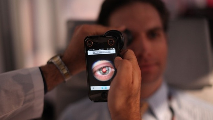 This image provided by TEDMED, shows a medical student preparing to photograph the inside of someone's eye using a special tool that taps a smartphoneâs camera during a recent TEDMED conference in Washington. Companies are developing a variety of miniature medical tools that hook onto smartphones to provide almost a complete physical. The hope is that this mobile medicine will help doctors care for patients in new ways, and also help people better monitor their own health. (AP Photo/TEDMED)