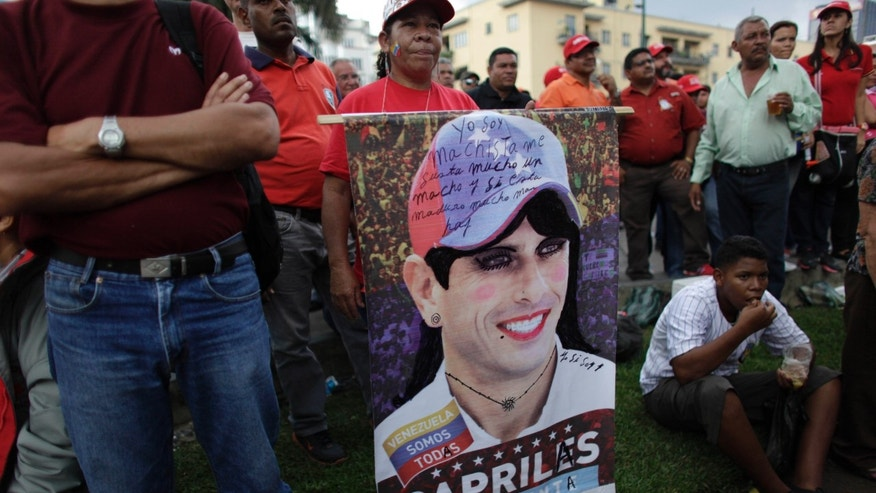 "In this photo taken May 1, 2013, supporters of the ruling party stand around a defaced poster of opposition presidential candidate Henrique Capriles during a May Day march in Caracas, Venezuela. Venezuelans have long been obsessed by politics, especially during the Chavez years, as the populist leader denounced his opponents as ""the squalid ones"" and the opposition tried vainly to oust him through a coup and a referendum. Many, however, say the tensions have reached a pitch not seen here since that 2002 coup, which briefly pushed Chavez from office. (AP Photo/Ariana Cubillos)"