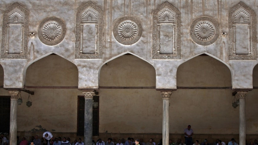 A boy plays in front men praying, background, during the Friday noon prayer in Al-Azhar mosque in Cairo, Egypt, Friday, May 10, 2013. (AP Photo/Khalil Hamra)
