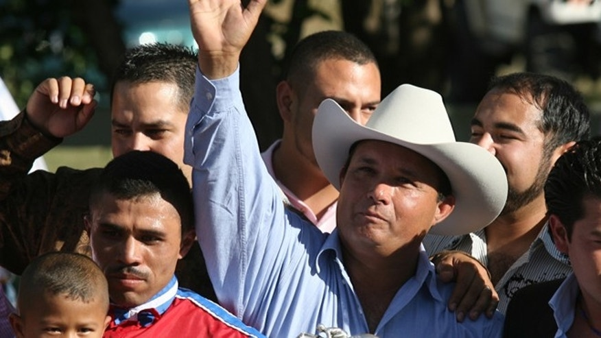 In this Sept. 6, 2010 file photo, owner José Treviño Morales, center, acknowledges the crowd as he stood with the trophy after Mr. Piloto won the All American Futurity horse race at Ruidoso Downs, N.M. (AP Photo/The El Paso Times, Rudy Gutierrez)