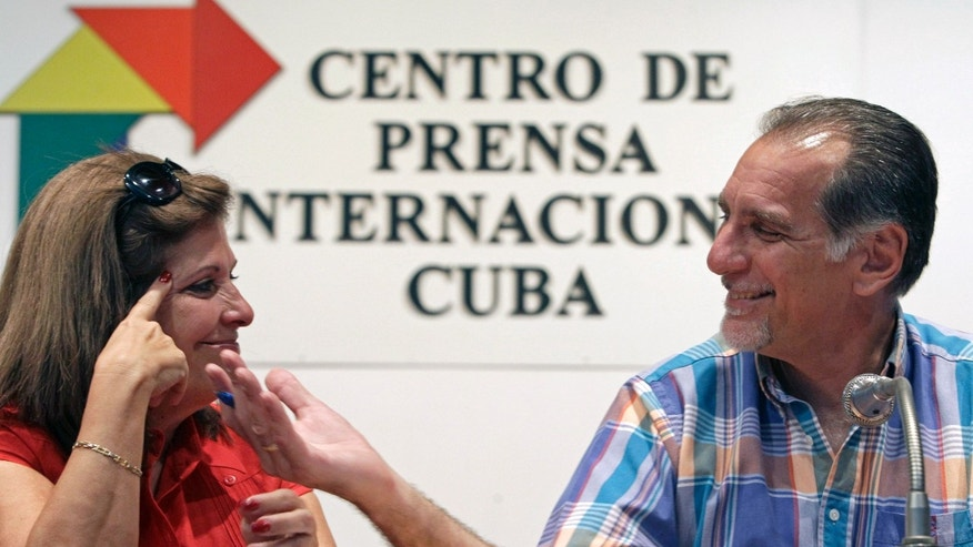 "Cuban agent Rene Gonzalez, 56, smiles at his wife Olga Salanueva during a press conference in Havana, Cuba, Friday, May 10, 2013. Gonzalez who spent 13 years in a U.S. prison renounced his American citizenship Monday, May 6, 2013, as part of a deal that allows him to avoid returning to the United States to serve out the remainder of his probation. Gonzalez, is one of the so-called ""Cuban Five"" intelligence agents convicted in 2001 of spying on U.S. military installations in South Florida, exile groups and politicians. (AP Photo/Franklin Reyes)"