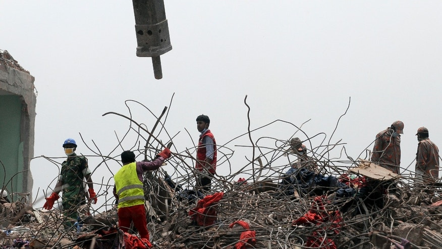 Rescuers work at the site of the eight-story Rana Plaza building that collapsed in Savar, near Dhaka, Thursday, May 9, 2013. The death toll from the collapse of the garment factory building passed 900 on Thursday even as a fire in an 11-story garment factory Wednesday night in Dhaka killed eight people, including a ruling-party politician and a top official in the country's powerful clothing manufacturers' trade group. (AP Photo/Ismail Ferdous)