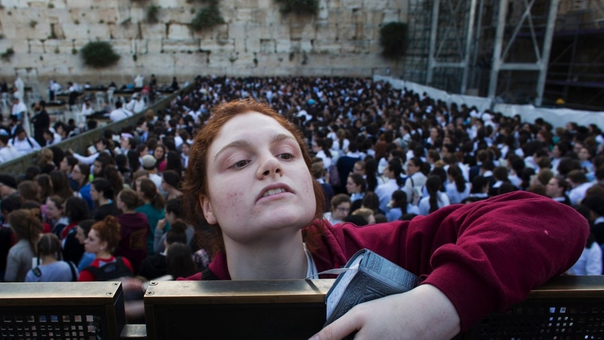 "May 10, 2013: A Jewish orthodox women follows a prayer organized by the ""Women of the Wall"" organization, not pictured, at the Western Wall, the holiest site where Jews can pray in Jerusalem's old city."