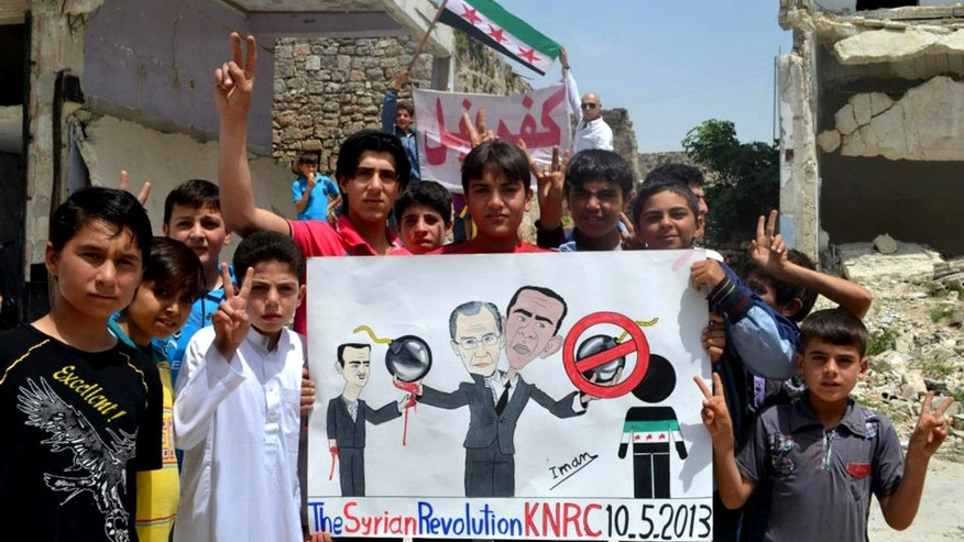 May 10, 2013: In this citizen journalism image provided by Edlib News Network, ENN, which has been authenticated based on its contents and other AP reporting, anti-Syrian regime protesters hold a poster depcting Syrian President Bashar Assad, left, Russian Foreign Minister Sergei Lavrov, center, and U.S. President Barack Obama, right during a demonstration, at Kafr Nabil town, in Idlib province, northern Syria.