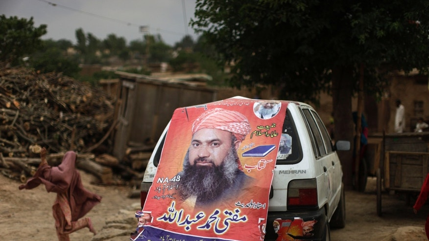 A Pakistani girl runs past a car decorated with an election banner showing Mohammed Abdullah, a candidate of a pro-Taliban religious group Jamiat-e-Ulema Islam (JUI-F) in a poor neighborhood on the outskirts of Islamabad, Pakistan, Friday, May 10, 2013. An especially violent spate of killings, kidnappings and bombings marred the run-up to Pakistan's nationwide election, capped Thursday by the abduction of the son of a former prime minister as he was rallying supporters on the last day of campaigning before the historic vote. (AP Photo/Muhammed Muheisen)