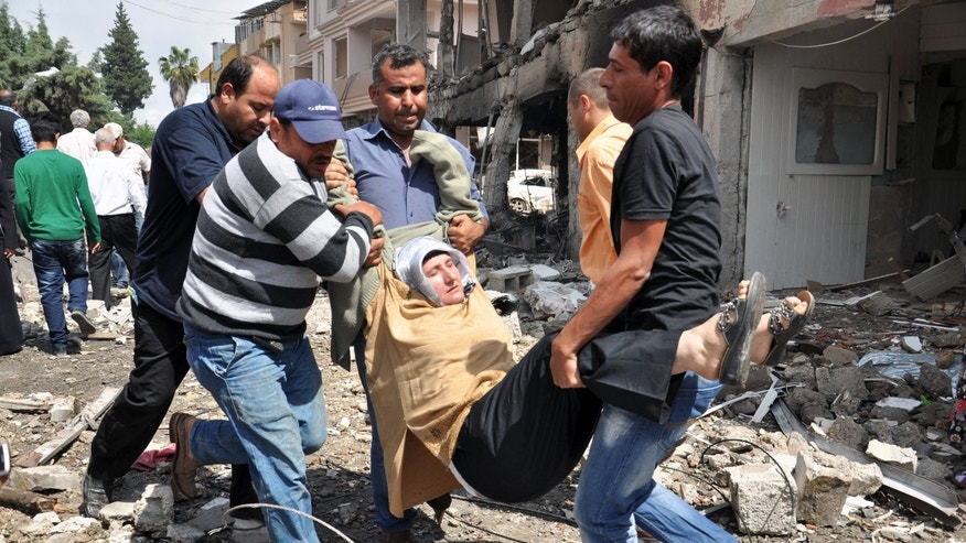 May 11, 2013: People carry a woman injured in a blast in Reyhanli, near Turkey's border with Syria.