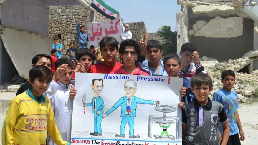 "In this citizen journalism image provided by Edlib News Network, ENN, which has been authenticated based on its contents and other AP reporting, anti-Syrian regime protesters hold a poster depicting Syrian President Bashar Assad, left, and Russian Foreign Minister Sergei Lavrov, right,  during a demonstration, at Kafr Nabil town, in Idlib province, northern Syria, Friday May 10, 2013. Arabic banner on the background reads, ""Kafr Nabil."" (AP Photo/Edlib News Network ENN)"