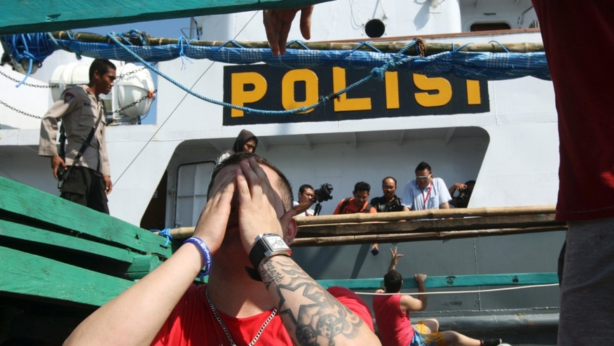 An Iranian asylum seeker reacts on a boat which was caught in Indonesian waters while sailing to Australia, at Benoa port in Bali, Indonesia, Sunday, May 12, 2013. More than 100 Iranians were on the boat en-route to Australia to seek for asylum when they were caught and detained by Indonesian authorities on Sunday. (AP Photo/Firdia Lisnawati)