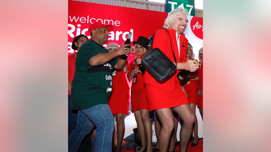 British business magnate Richard Branson, right, dressed up as an AirAsia flight attendant, and AirAsia's Chief Executive Tony Fernandes prepare to spray champagne during an AirAsia promotional event after Branson arrived at the low cost carrier terminal in Kuala Lumpur, Malaysia, Sunday, May 12, 2013. The Virgin Group founder had his legs shaved, put on lipstick and squeezed into the red skirt to honor a bet by serving as a flight attendant on an AirAsia trip from Perth, Australia, to Malaysia. Branson lost a bet to Fernandes in 2010 after they both wagered their Formula One racing teams would finish ahead of each other. (AP Photo/Vincent Thian)