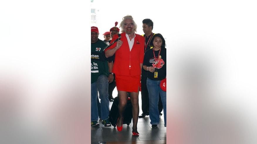 British entrepreneur Richard Branson arrives at a low cost carrier terminal dressed up as an AirAsia stewardess from a flight from Australia to Malaysia, Sunday, May 12, 2013. Branson wore the costume after losing a bet with his friend AirAsia's Chief Executive Tony Fernandes on which of their 2010 Formula One racing car teams would finish ahead of the other. (AP Photo/Vincent Thian)