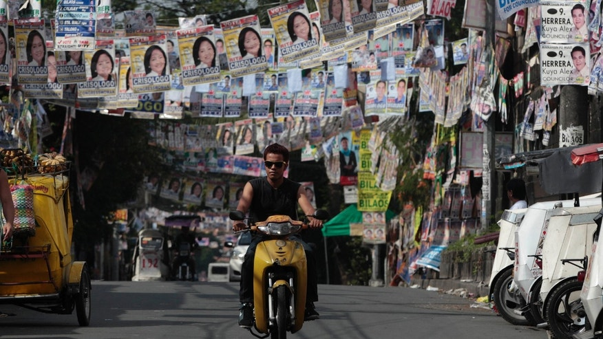 A Filipino man rides his motorcycle past layers of election posters in suburban Quezon city, north of Manila, Philippines on Sunday May 12, 2013. The country will elect local officials from senators to congressmen and down to municipal mayors on Monday's mid-term elections. (AP Photo/Aaron Favila)