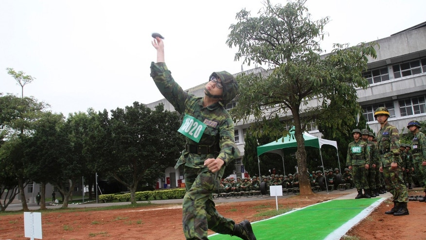 In this photo taken on April 22, 2013, a new recruit practices throwing grenades at a military training center in Hsinchu County, northern Taiwan. A Taiwanese plan to end mandatory military service and shift to an all-volunteer force is running into a problem: Not enough volunteers. Such forces are generally considered superior to conscripted ones, because those serving want to be there. Recruitment is proving difficult in a prosperous society that offers young people alternatives and doesn't glorify military service. (AP Photo/Chiang Ying-ying)