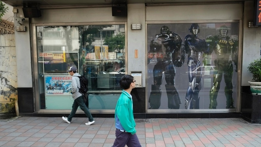 "In this March 22, 2013 photo, young men pass a military recruitment center using ""Transformer"" robots to attract young Taiwanese to volunteer in Taipei, Taiwan. A Taiwanese plan to end mandatory military service and shift to an all-volunteer force is running into a problem: Not enough volunteers. Such forces are generally considered superior to conscripted ones, because those serving want to be there. Recruitment is proving difficult in a prosperous society that offers young people alternatives and doesn't glorify military service.  (AP Photo/Wally Santana)"