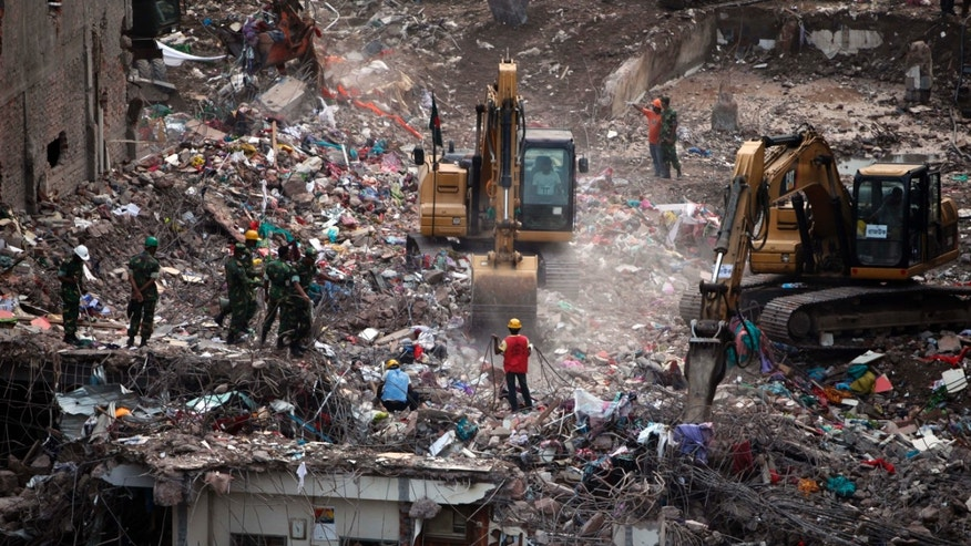 May 12, 2013 - Bangladeshi rescuers use heavy machinery to clear rubble of a garment factory building that collapsed on April 24 in Savar, Bangladesh.