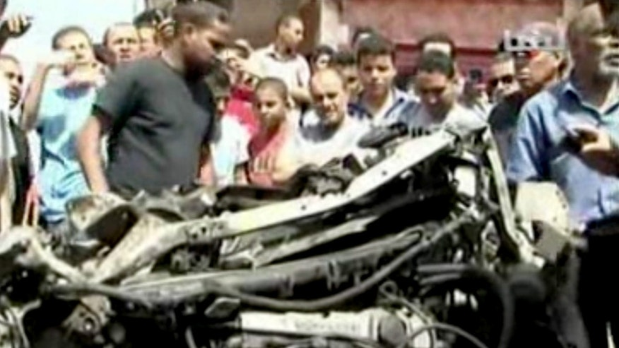 In this image made from pool video provided by APTN, Libyan men inspect a destroyed car at the scene of a car bomb explosion in Benghazi, Libya, Monday, May 13, 2013. A car bomb exploded Monday near a hospital in the eastern Libyan city of Benghazi, killing many, officials said, in one of the biggest attacks since the end of the civil war that ousted former dictator Moammar Gadhafi. (AP Photo/APTN, Al Ahrar)