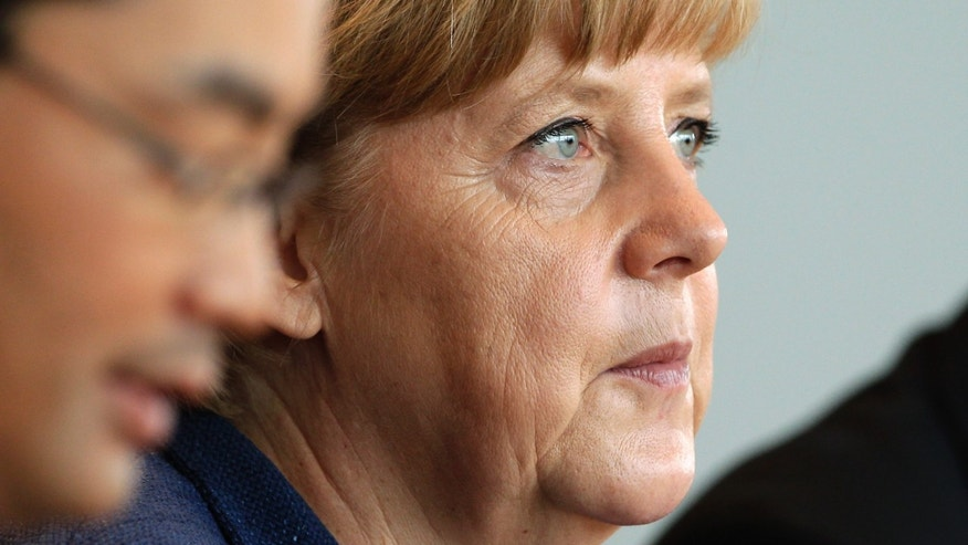 German Chancellor Angela Merkel attends the weekly cabinet meeting at the chancellery in Berlin, Germany, Wednesday, May 8, 2013. At left is German Economy Minister Philipp Roesler. (AP Photo/Michael Sohn)