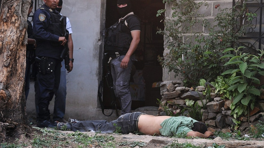 April 7, 2013: In this file photo, police stand next to the body of a man who was killed during a shootout with police who were carrying out an offensive against gang members in Tegucigalpa, Honduras.