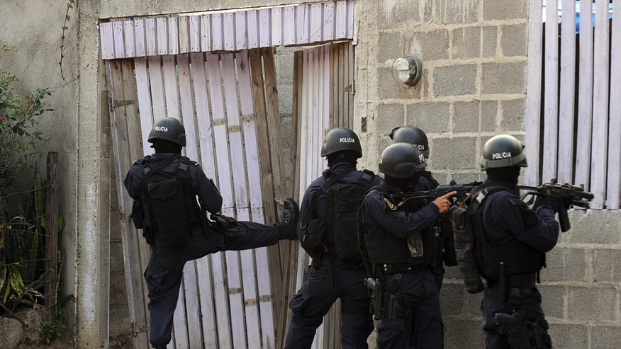 April 7, 2013: In this file photo, police break into a home during a shootout that ended in two suspects killed and one officer injured as police carry out an offensive against gang members in Tegucigalpa, Honduras.