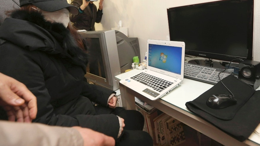 "In this photo taken on Dec. 13, 2012, a National Intelligence Service agent covered her face with a mask sits in front of her computers as officers from police and national election commission visit her to collect evidence from her computers at her home in Seoul, South Korea. The scandal shaking up South Korea's main spy agency is not cloak-and-dagger stuff, but the kind of low-grade trickery anyone with an Internet connection could pull off. And the target was not Seoul's opaque rival to the north, but the country's own people. Internet postings ostensibly from ordinary South Koreas, but actually from National Intelligence Service agents, allegedly boosted President Park Geun-hye while she was running for the job as the ruling party's nominee. She was reportedly dubbed ""the best,"" while her opponent, in a play on his name, was called ""criminal."" (AP Photo/Yonhap, Im Hun-jung) KOREA OUT"