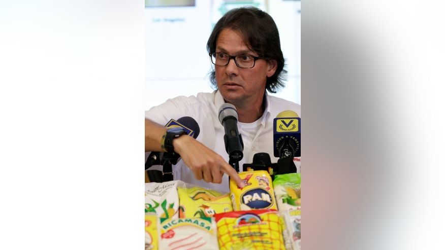 "Empresas Polar chief executive Lorenzo Mendoza points to a bag of corn flour as he gives a news conference at his office in Caracas, Venezuela, Monday, May 13, 2013. Mendoza said Monday that, in his words, ""the accusations that we are producing less than last year are false,"" rejecting President Nicolas Maduro's claims that it's to blame for the country's persistent food shortages. Mendoza offered to buy or rent government-owned corn processing plants to increase Venezuela's production, and food makers say shortages of basic foods like sugar, milk, butter and cornmeal stem from the socialist government's price controls and a lack of foreign currency to pay for imports. (AP Photo/Fernando Llano)"