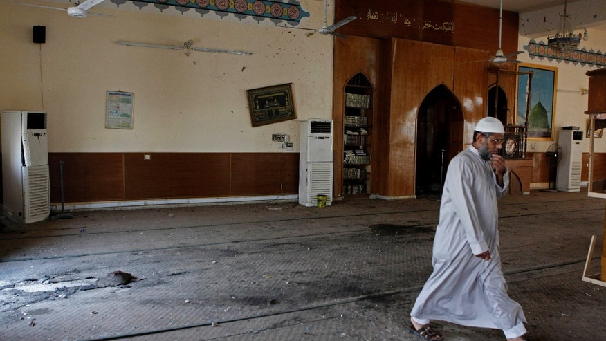 In this Wednesday, May 8, 2013 photo, an Iraqi cleric walks inside a damaged Sunni mosque in western Baghdad, Iraq. Attacks on mosques, especially where Sunnis worship, have been on the rise recently. Iraqi officials have warned that insurgents are trying to take advantage of the country's political and sectarian turmoil by targeting mosques in an attempt to reignite civil strife in the country. The mosque was attacked two weeks ago. (AP Photo/Hadi Mizban)