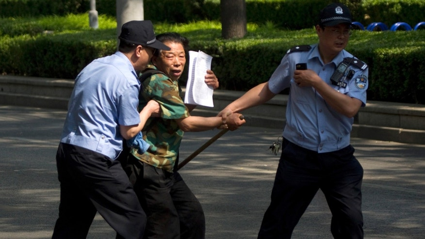 "FILE - In this May 8, 2012 photo, a petitioner trying to attract public attention is taken away by policemen outside a hospital where blind activist Chen Guangcheng is kept in Beijing, China. Chinese authorities have shut down or frozen the microblog accounts of several prominent liberal intellectuals and harassed rights lawyers lobbying against unofficial ""black jails,"" underlining the determination of the country's new leadership to control dissent even as it vows to root out corruption. (AP Photo/Alexander F. Yuan, File)"