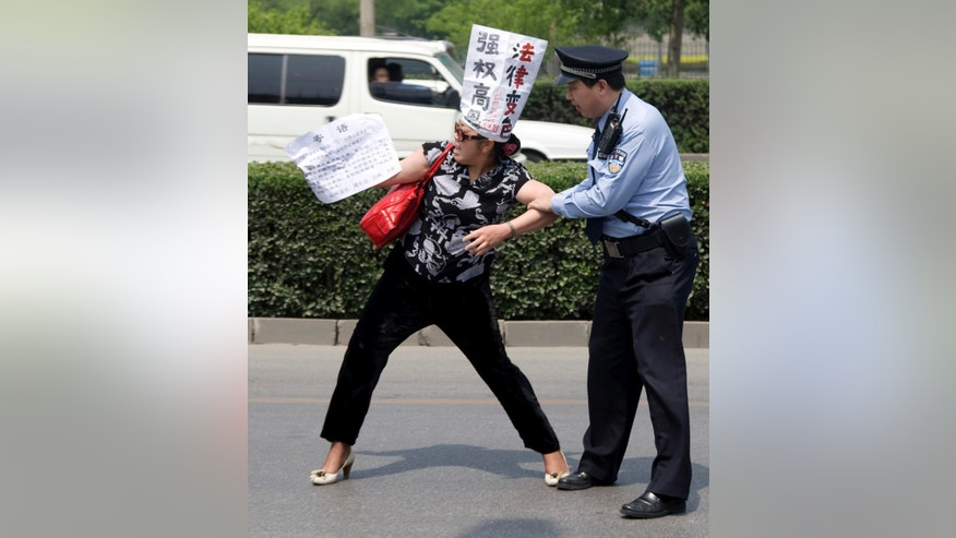 "FILE - In this May 4, 2009 file photo, a Chinese police officer tries to restrain a Chinese petitioner protesting against corruption and legal injustice on a road near a hotel in Beijing, China. Chinese authorities have shut down or frozen the microblog accounts of several prominent liberal intellectuals and harassed rights lawyers lobbying against unofficial ""black jails,"" underlining the determination of the country's new leadership to control dissent even as it vows to root out corruption. (AP Photo/Ng Han Guan, File)"