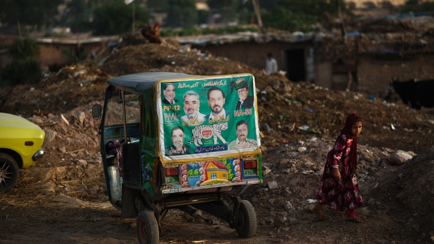 "A Pakistani girl, right, who was displaced with her family from Pakistan's tribal areas due to fighting between militants and the army, walks past an election banner showing former prime minister and leader of Pakistan Muslim League-N, Nawaz Sharif, and other members of his party, pasted on a rickshaw parked in a poor neighborhood on the outskirts of Islamabad, Pakistan, Monday, May 13, 2013. Nawaz Shari, the Pakistani politician poised to become the country's next prime minister said Monday that Islamabad has ""good relations"" with the United States, but called the CIA's drone campaign in the country's tribal region a challenge to national sovereignty. (AP Photo/Muhammed Muheisen)"