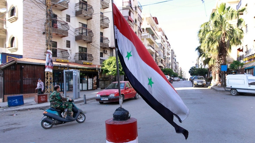 In this Tuesday, April. 30, 2013 photo, a Lebanese army soldier rides a motorcycle, and passes in front of Syrian flag, in the predominantly Alawite neighborhood of Jabal Mohsen in the northern port city of Tripoli, Lebanon.  Lebanese members of the Syrian leader's Alawite sect fear their tiny community will be a casualty of the civil war raging in the neighboring country. Already, Sunni extremists have stoned a school bus, vandalized stores and beaten or stabbed a number of men in a wave of attacks against Lebanese Alawites, raising fears of more violence should Assad be removed from power. (AP Photo/Bilal Hussein)