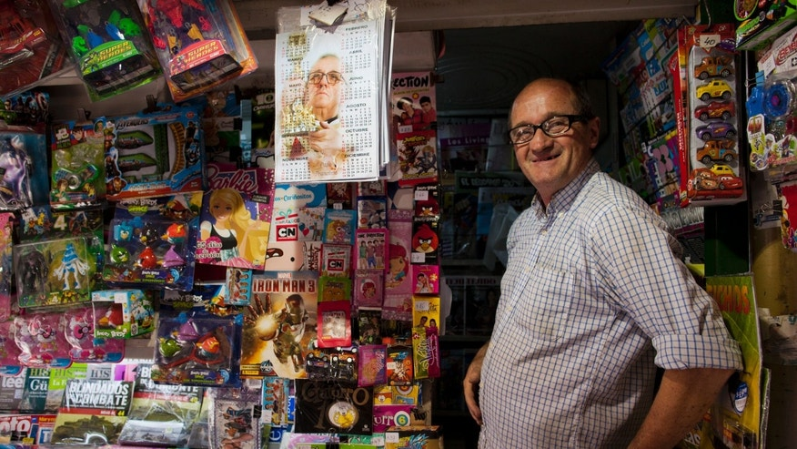 In this May 11, 2013 photo, newspaper vendor Nicolas Schandor smiles from his kiosk where he also sells calendars featuring Pope Francis in Buenos Aires, Argentina. With an Argentine on the throne of St. Peter, the South American country's capital city has launched a series of guided tours, that include Schandor's news stand, where the former archbishop used to buy the newspaper on the weekends. The three-hour weekend bus trips are a modest, and so far non-commercial first step at papal tourism. The tour bus winds through Buenos Aires twice each Saturday and Sunday and can carry about 40 passengers, cruising past 24 sites linked to the new pope. (AP Photo/Natacha Pisarenko)