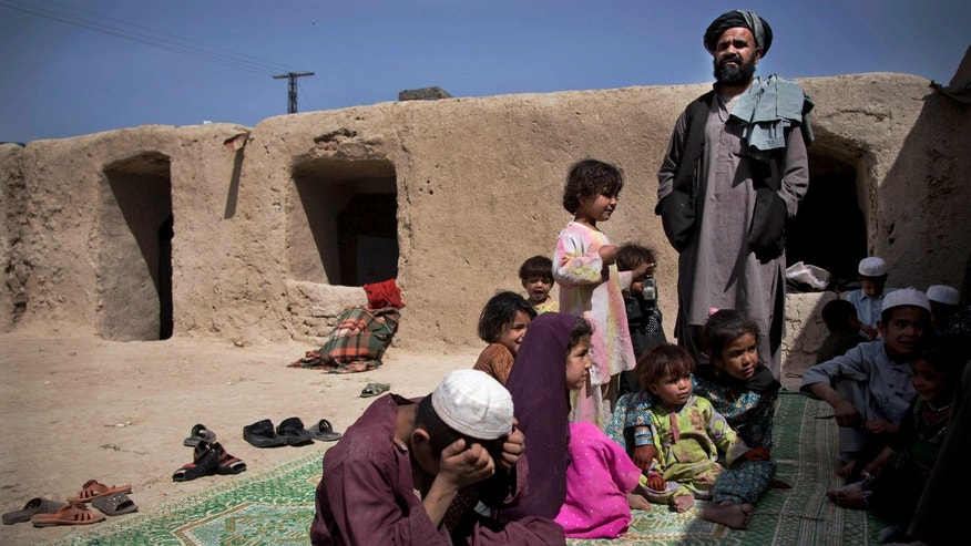 Maulvi Mohammed Baran, right, the brother-in-law of Masooma, whose husband was killed on March 11, 2012, stands at his home on the outskirts of Kandahar, Afghanistan surrounded by his children and Masooma's children. In an interview, Masooma recounted the events of pre-dawn March 11, 2012 when a U.S. soldier rampaged through two villages killing 16 people, including her husband. (AP Photo/Anja Niedringhaus)