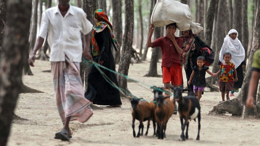 Bangladeshis carry their belongings and leash precious animals as they walk towards a cyclone shelter centre, ahead of the coming of tropical cyclone Mahasen, in Chittagong, Bangladesh, Wednesday, May 15, 2013.  People living in coastal areas in Bangladesh and Myanmar are being evacuated as cyclone Mahasen is predicted to make landfall late Thursday or early Friday, according to news reports. (AP Photo/Anurup Titu)